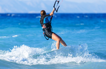 young woman kite-surfer rides in greenish-blue sea under clear skies