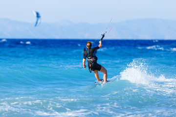 young woman kite-surfer rides in summer day