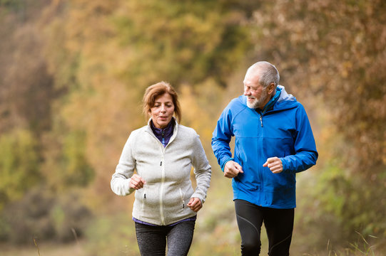 Beautiful senior couple running outside in sunny autumn forest