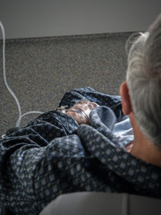 Old patient man with iv drip in the hand