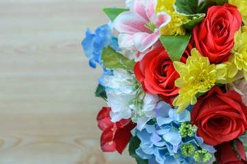 Colorful decoration artificial flower on wood background