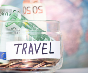 Travel budget concept. Travel money savings in a glass jar with world map on background