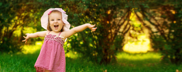 Smiling little girl in a meadow in the park.