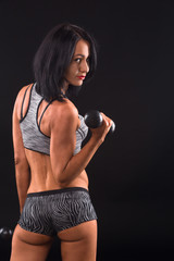 Sports concept. Pretty brunette fitness lady training with dumbbells and showing her muscular biceps and body in general in studio.