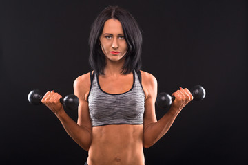 Sports and bodybuilding concepts. Fitness woman posing with dumbbells in both hands while posing for photographer isolated on black in studio.