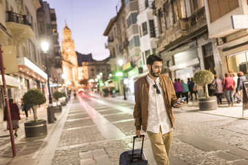 Man with suitcase and cell phone at night in the city