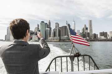 USA, Brooklyn, back view of businesswoman on a boat taking picture of Manhattan skyline