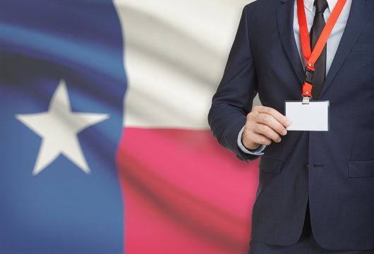 Businessman holding badge on a lanyard with USA state flag on background - Texas