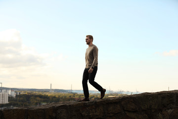 Man wearing a brown sweater and jeans, walking along a mountain top with the great cityview behind him on a summer day. Looking away from camera.
