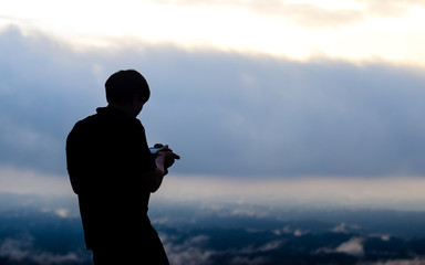silhouette of the man. in his hand have a camera. he is taking a photo.