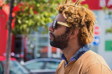 Portrait of young black man with dread locks wearing sunglasses.