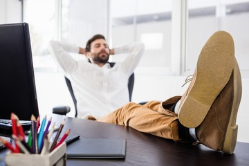 Relaxing man with his leg crossed on the desk