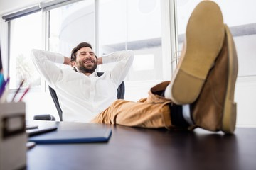A smiling man relaxing in the office