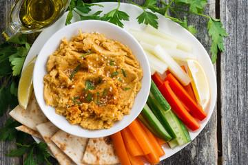 Arabic sauce hummus with flatbread and fresh vegetables, closeup