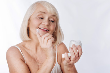 Nice good looking woman putting anti age cream