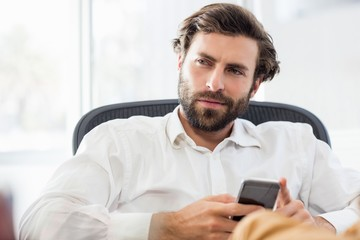 A thinking man holding his phone