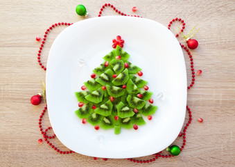 Christmas healthy dessert idea for kids party - funny edible kiwi pomegranate Christmas tree, beautiful New Year background, top view blank space for text
