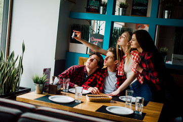 friends make selfie in a cafe. Two boys and two girls make selfie in cafe