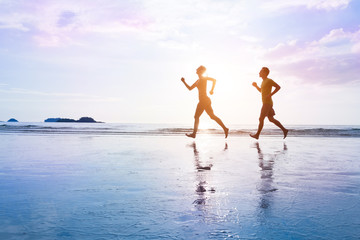 Healthy lifestyle. Young couple are jogging on beautiful sunset sea beach. Sporty family concept.