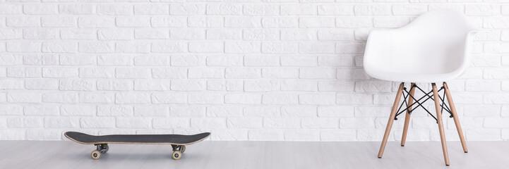 Brick wall, armchair and skateboard