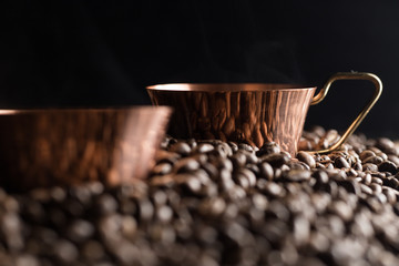 Two bronze cup full of coffee on the grains pile. Italian traditional morning short drink on breakfast. Close-up.