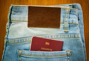 passport inside denim jeans pocket with brown leather tag