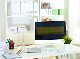 Designer working desk with a computer and paperwork