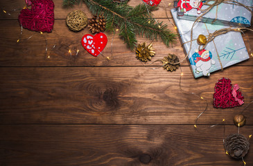 Christmas wooden background with christmas decorations and objects Christmas gift box, fir tree branches, hearts, cones. garland Free space