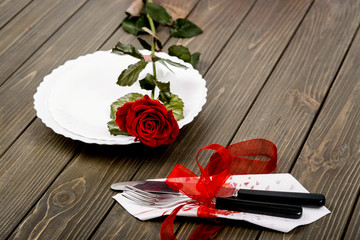 Red rose lies on white dinner plate before fork and knife decora