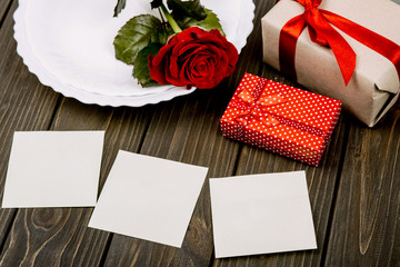 White empty cards lie before present boxes and dinner plate with