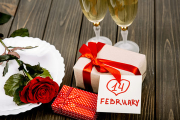 Card with lettering '14 february' lies on present box before pla
