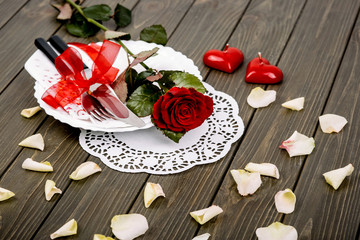 White petals surround dinner plate with red rose on it