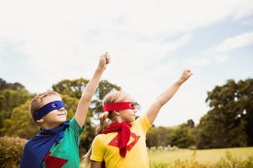 Two cute children pretending to fly in superhero costume