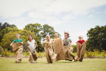 Children having a sack race in park