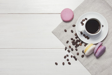Wooden background with coffee and macaroons.