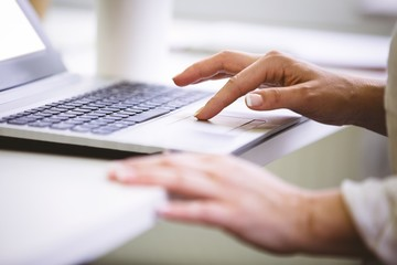 Cropped image of businesswoman using laptop at office