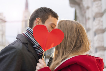 Young Couple in Love Kissing Behind Red Heart. Love and Valentines Day Concept.