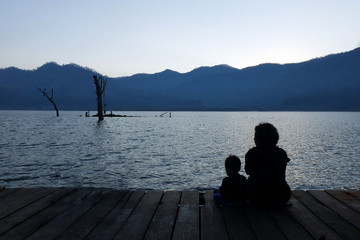 Silhouette mother and child watching the natural scenery.copy space