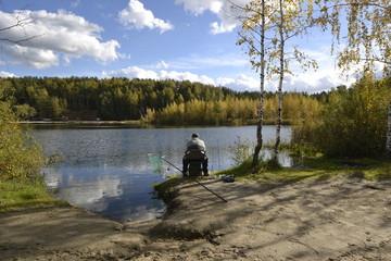 Рыбак сидит на берегу