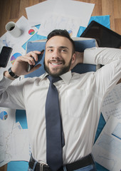 young businessman freelancer working remotely at home  lies and talking on the phone smiling