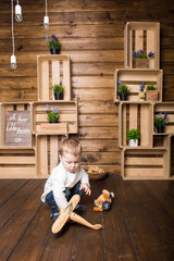 a boy playing with a toy inside a decorated wooden house