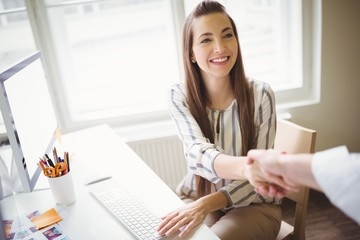 Person shaking hands with businesswoman in office