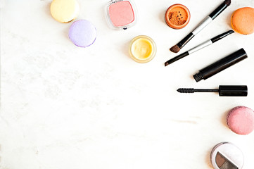Flat lay of fashion makeup products on a marble background.