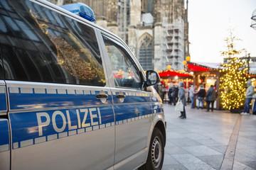 Einsatzwagen der Polizei parkt vor einem weihnachtsmarkt