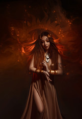 Beautiful, red-haired girl - a priestess of the sun. Dress and jewelry in ethnic style. Unusual make-up in orange and gold tones. Girl praying in silence.  Fantastic photography