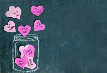 Pink paper cutout hearts are floating out of drawing of a jar out of white chalk on a rough textured slate background. Messages added to hearts for Valentine's Day. Copy space.