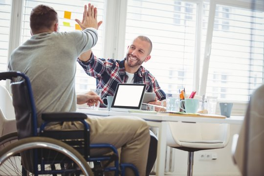 Handicap businessman giving high-five to colleague in office