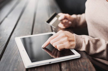 Hands holding credit card and using digital tablet. Online shopping concept