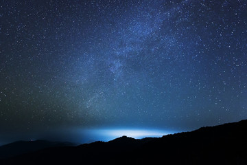Milky way and bright cloud over the mountain