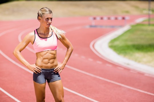 Female athlete standing with hand on hips on the running track